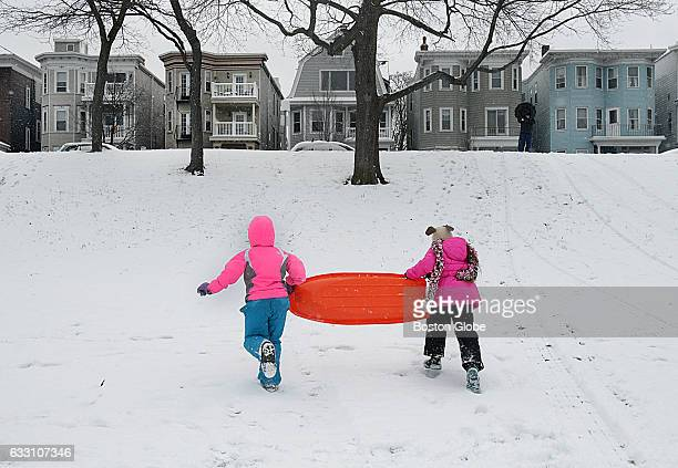 Mia Vacha and Lorelai Davis both 9 and from Medford climb a steep enough hill in South Boston to get in some last sledding for the season on the...