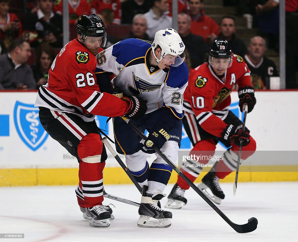Miachal Handzus #26 of the Chicago Blackhawks, playing in the 1000th game of his career, pressures Dmitrij Jaskin #26 of the St. Louis Blues at the United Center on March 19, 2014 in Chicago, Illinois.