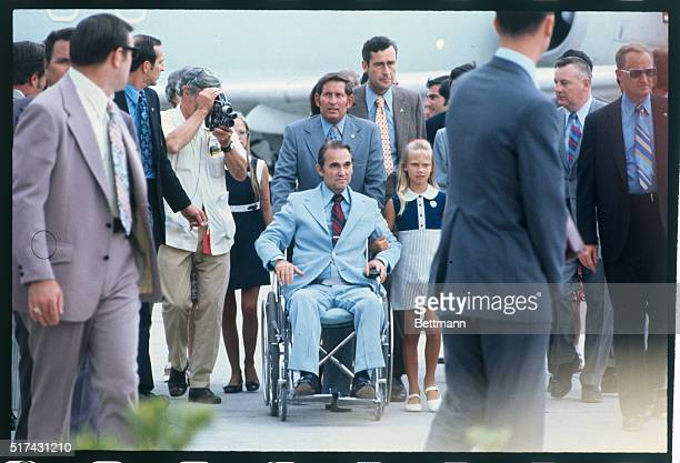 Governor George Wallace of Alabama is wheeled to press conference after his arrival at Miami Airport Also he is shown talking to group at airport He...