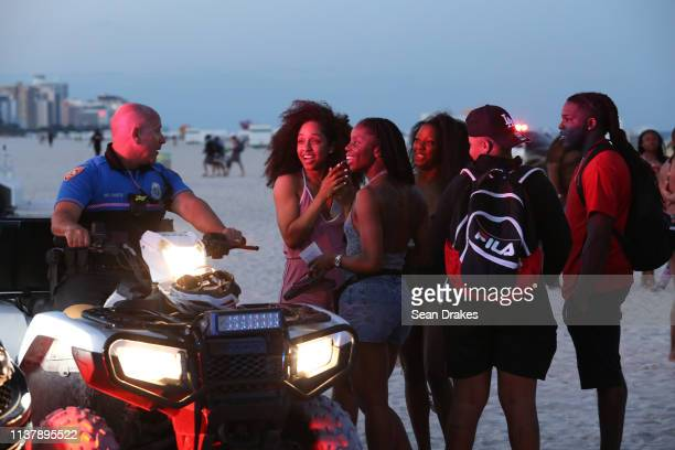 Miami Beach Police Officer Canete chats with beachgoers attending Spring Break festivities in Miami Beach on March 23 2019 in Miami Florida USA