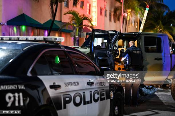 Miami Beach police officer inspects the inside of a car on Ocean Drive in Miami Beach, on March 22, 2021. - The US city of Miami Beach, overrun by...