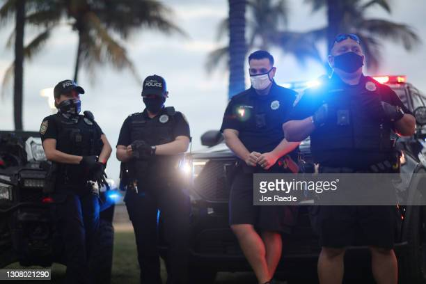 Miami Beach police officers keep an eye on people along Ocean Drive on March 19, 2021 in Miami Beach, Florida. College students have arrived in the...