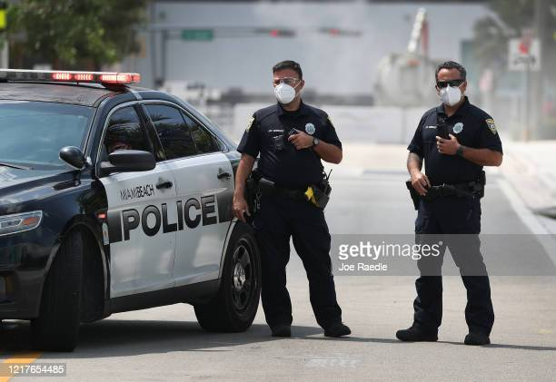 Miami Beach police officers wear protective masks as Florida Gov Ron DeSantis along with other officials and politicians speak during a press...