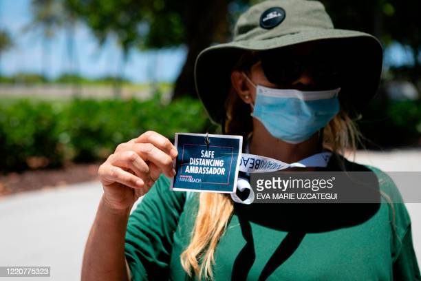 """Miami Beach worker shows her badge as """"Safe Distancing Ambassador"""" at the entrance to the beach in Miami Beach, Florida on June 16, 2020. - Florida..."""