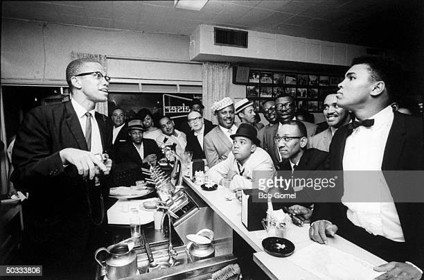 Black Muslim leader Malcolm X behind soda fountain joking with tuxclad Cassius Clay who responds with mock indignation while surrounded by jubilant...