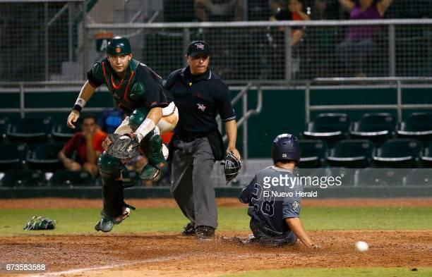 Miami catcher Joe Gomez evades the slide of Florida International's Adam Sevario during the ninth inning at Alex Rodriguez Park at Mark Light Field...