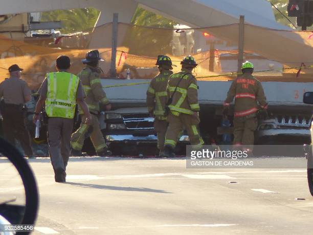 Miami Dade fire rescue personnel work the scene of a pedestrian bridge collapse in Miami Florida on March 15 crushing a number of cars below and...