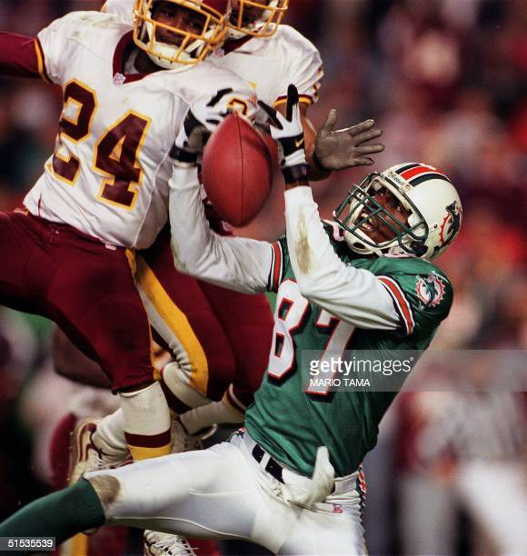 Miami Dolphin wide receiver Yatil Green leaps for a pass as Washington Redskin cornerback Champ Bailey defends on the final play of the first half at...