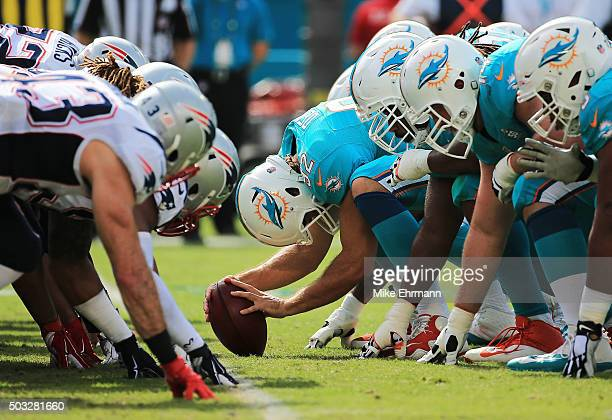 Miami Dolphins and New England Patriots players line up before a snap during the first quarter of the game at Sun Life Stadium on January 3 2016 in...