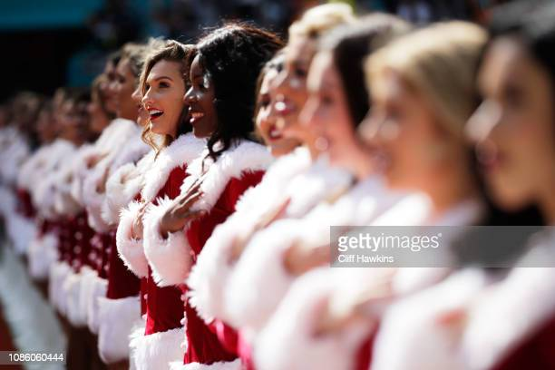 Miami Dolphins cheerleaders dressed in Christmas costumes look on during the national anthem prior to their game against the Jacksonville Jaguars at...