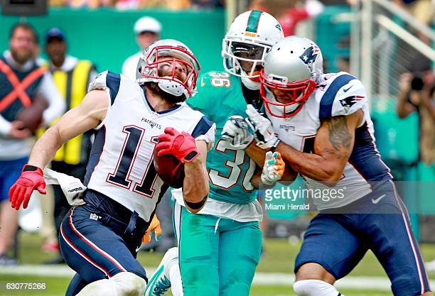 Miami Dolphins defensive back Tony Lippet is blocked by New England Patriots wide receiver Michael Floyd springing Julian Edelman for a 77yard...