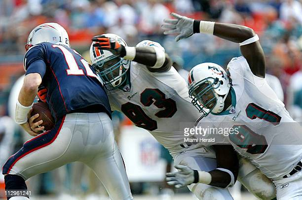 Miami Dolphins defensive end Kevin Carter center and defensive tackle Vonnie Holliday sack New England Patriots quarterback Tom Brady in the second...
