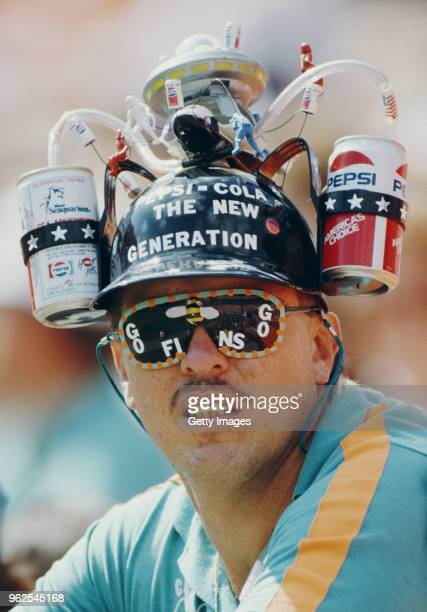 A Miami Dolphins fan hold wears a hat adorned with two Pepsi cans to drink from during the American Football Conference East game against the New...
