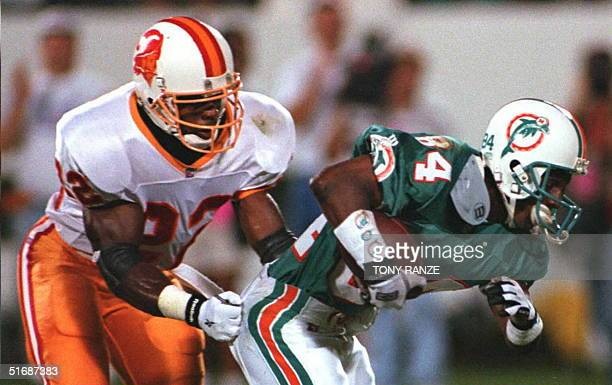 Miami Dolphins Gary Clark can't escape the grip of Tampa Bay Buccaneers Thomas Everett as he runs for yardage during the first quarter of the game at...