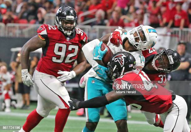 Miami Dolphins' Jarvis Landry catches the ball to advance the ball to help score the winning field goal in the fourth quarter as he is hit by Atlanta...