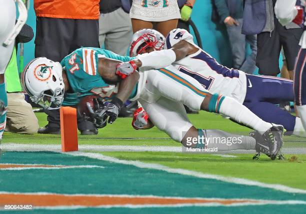 Miami Dolphins' Jarvis Landry scores a second qaurter touchdown as New England Patriots' Jonathan Jones attempts to tackle him at Hard Rock Stadium...