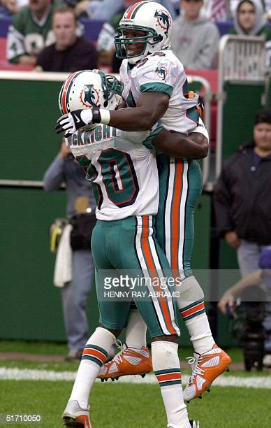 Miami Dolphins LaMont Jordan is hugged by teammate James McKnight after Jordan scored the Dolphins second touchdown on a 28yard screen pass in the...