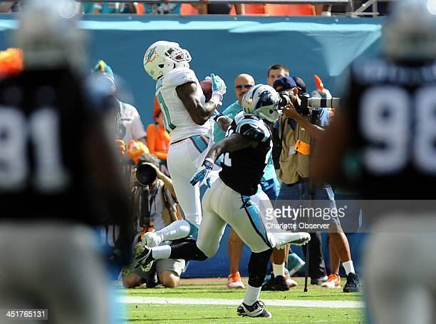 Miami Dolphins' Mike Wallace hauls in a touchdown pass over Carolina Panthers' Captain Munnerlyn during the first half at Sun Life Stadium Miami...