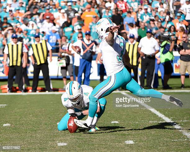Miami Dolphins Place Kicker Andrew Franks kicking an extra point with Miami Dolphins Punter Matt Darr holding during the NFL football game between...
