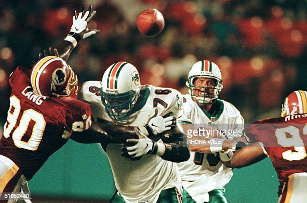 Miami Dolphins' quarter back Dan Marino passes through the defense of Washington Redskins' defensive ends Kenard Lang and Chris Mimms with help of...