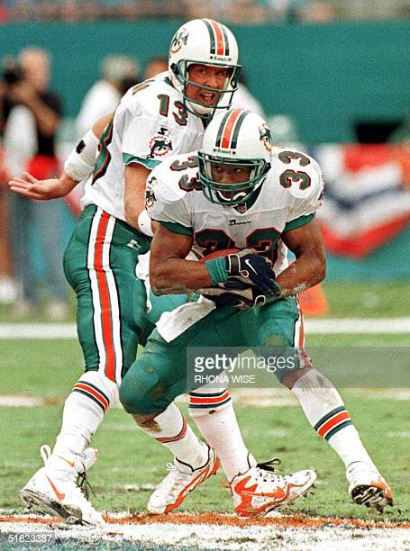 Miami Dolphins quarterback Dan Marino hands off to running back Karim AbdulJabbar during second quarter action in their divisional AFC Wild Card...