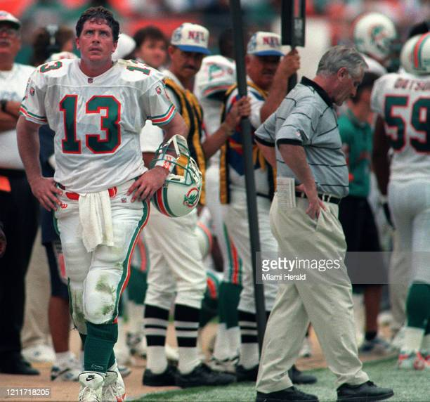 Miami Dolphins quarterback Dan Marino walks on the sidelines looking at the scoreboard as coach Don Shula drops his head after Marino threw an...