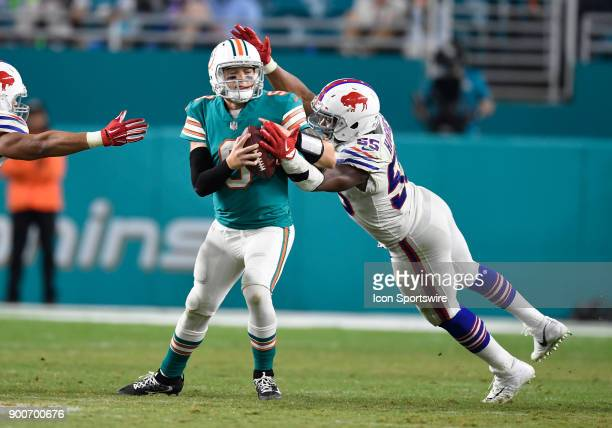 Miami Dolphins quarterback David Fales avoids a sack from Buffalo defensive lineman Jerry Hughes during an NFL football game between the Buffalo...