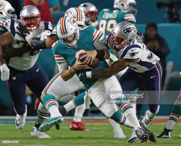 Miami Dolphins quarterback Jay Cutler escapes the grasp of New England Patriots safety Jordan Richards to complete a pass for a first down during the...