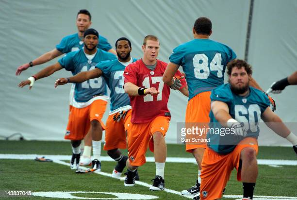 Miami Dolphins quarterback Ryan Tannehill, center, warms up during rookie camp practice at the team's practice facility in Davie, Florida, on Friday,...