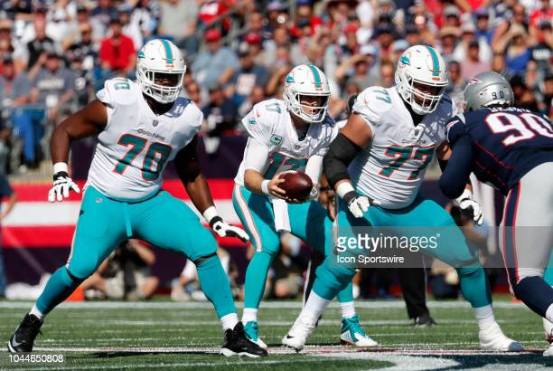 Miami Dolphins quarterback Ryan Tannehill fields a snap as Miami Dolphins offensive tackle Ja'Wuan James and Miami Dolphins offensive tackle Jesse...