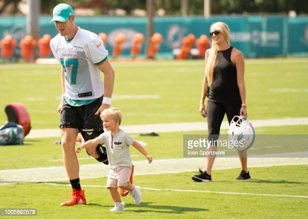 Miami Dolphins Quarterback Ryan Tannehill runs with his twoyearold son Steel Tannehill on the field followed by his wife Lauren Tannehill after a...