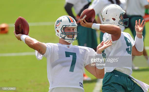 Miami Dolphins quarterbacks Chad Henne and Pat Devlin throw during a training camp workout on Saturday, July 30 at the team's training facility in...