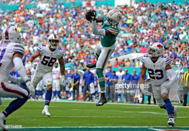 Miami Dolphins receiver DeVante Parker catches a first quarter touchdown as Buffalo Bills Matt Milano and Micah Hyde fail to defend on Sunday Dec 2...