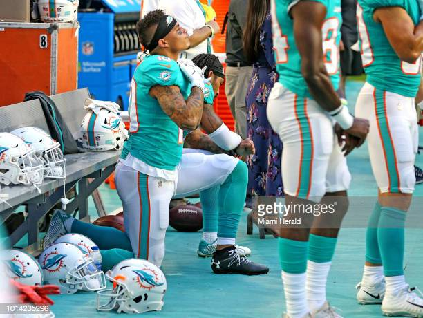 Miami Dolphins receivers Kenny Stills and Albert Wilson kneel during the national anthem as they prepare to play the Tampa Bay Buccaneers at Hard...