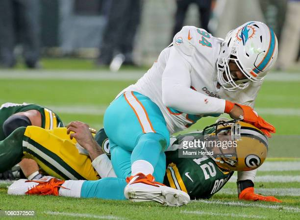 Miami Dolphins' Robert Quinn taps Green Bay Packers quarterback Aaron Rodgers on the helmet after a second quarter sack on Sunday Nov 11 2018 at...
