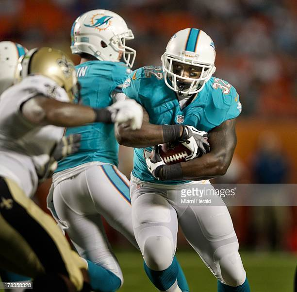 Miami Dolphins running back Jonas Gray runs the ball in the first quarter of a preseason game against the New Orleans Saints at Sun Life Stadium in...