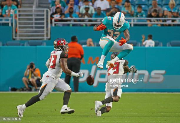 Miami Dolphins running back Kalen Ballage jumps as he fumbles against Tampa Bay Buccaneers cornerback Ryan Smith and safety Chris Conte during the...
