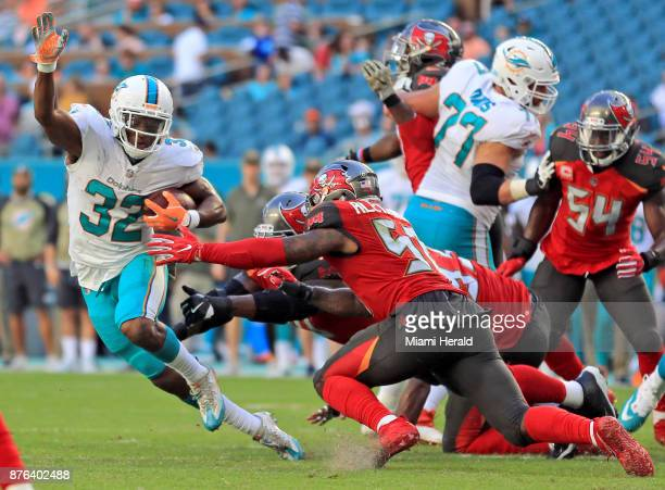 Miami Dolphins running back Kenyan Drake avoids the reach of Tampa Bay Buccaneer defenders in the third quarter on Sunday Nov 19 2017 at Hard Rock...