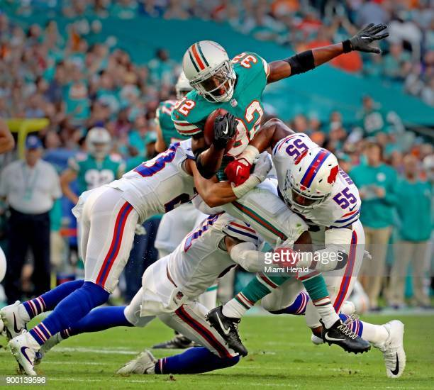 Miami Dolphins running back Kenyan Drake is tackled by the Buffalo Bills' Micah Hyde and Jerry Hughes in the first quarter at the Hard Rock Stadium...