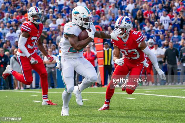 Miami Dolphins Running Back Mark Walton runs with the ball and straight arms Buffalo Bills Safety Micah Hyde defending during the first half of the...