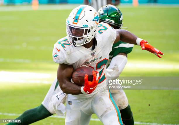 Miami Dolphins Running Back Mark Walton runs with the ball past New York Jets Linebacker Brandon Copeland during the NFL game between the New York...