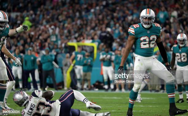 Miami Dolphins safety TJ McDonald celebrates stopping New England Patriots running back Dion Lewis for no gain on a play during the second half of a...