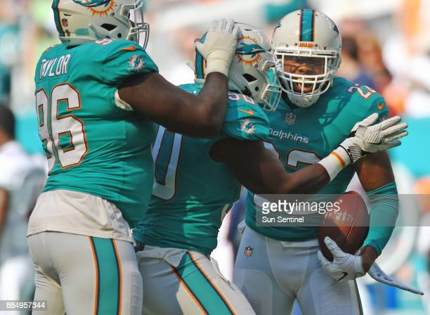 Miami Dolphins strong safety T.J. McDonald celebrates an interception with teammates Charles Harris and Vincent Taylor against the Denver Broncos on...