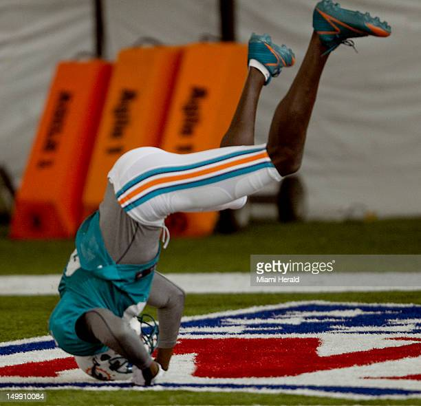 Miami Dolphins wide receiver Chad Johnson takes a headstand after missing a pass in drills at Dolphins training camp at NSU in Davie Florida Monday...