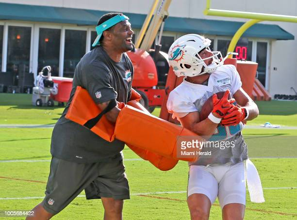 Miami Dolphins wide receiver Danny Amendola gets hit by assistant coach Shawn Jefferson during the first day of training camp at the Miami Dolphins...