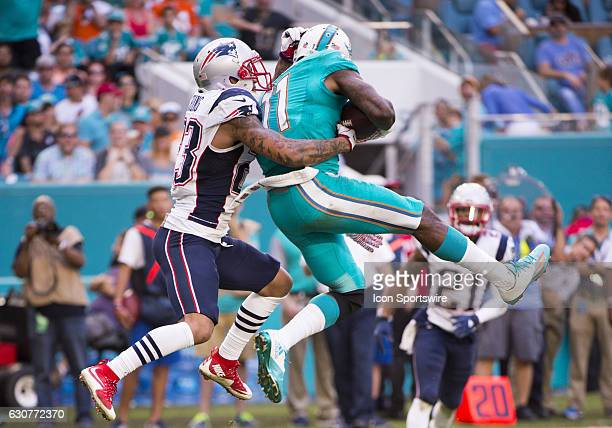 Miami Dolphins Wide Receiver DeVante Parker leaps up in the air to catches the ball in front of New England Patriots Safety Patrick Chung during the...