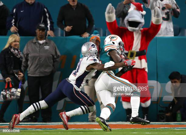 Miami Dolphins wide receiver Jarvis Landry right scores on a touchdown reception despite the efforts of New England Patriots cornerback Jonathan...