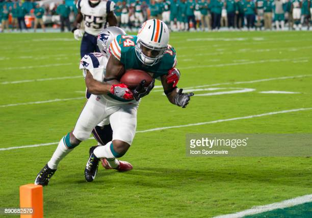 Miami Dolphins Wide Receiver Jarvis Landry runs into the end zone to score a touchdown as New England Patriots Cornerback Jonathan Jones tries to...
