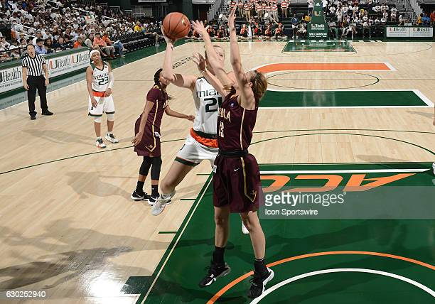 Miami forward/center Emese Hof shoots against Loyola guard/forward Katie Salmon during an NCAA basketball game between Loyola Chicago University...