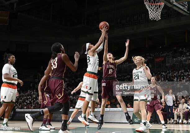 Miami guard Adrienne Motley grabs a rebound against Loyola guard/forward Katie Salmon during an NCAA basketball game between Loyola Chicago...